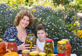 Mom with her son and home canned vegetables — Stock Photo