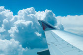 Wing of an airplane flying above the clouds. — Stock Photo