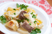 Baked potatoes with meat in a creamy sauce — Stock Photo