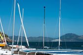 Mast sailing catamaran on a background of sea and mountains — Stock Photo