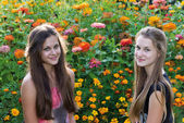 Teen girls on a background of flowers — Stock Photo