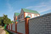 Wonderful family house a brick fence — Stock Photo
