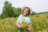 Middle-aged woman on a meadow with tansy — Stock Photo