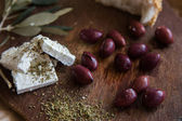 Olives on a wooden table and feta cheese — Stock Photo