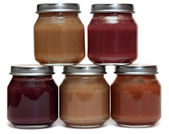 Five jars of baby food and spoon — Stock Photo