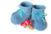 Pair of blue knit children's bootees and baby's dummy on a white background — Stock Photo