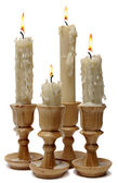 Four burning candles in wooden candlesticks — Stock Photo