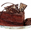 Piece of chocolate cake with icing on white isolated background — 图库照片
