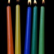 Burning of multi-colored candles on black background. Five. — Stock Photo #37747793