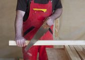 Carpenter work with a saw — Стоковое фото