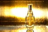 Botella de perfume sobre fondo de oro — Foto de Stock