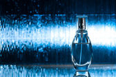 Perfume on blue background — Stock Photo