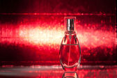 Bottle of perfume on red background — Stock Photo