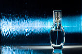 Bottle of perfume on blue background — Stock fotografie