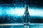 Perfume on blue shiny background — Stock Photo