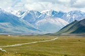 Dirt road in majestic Tien Shan mountains — Stock Photo