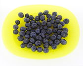 Blueberries on yellow plate — Stock Photo