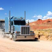 Semi-truck driving across the desert — Stock Photo