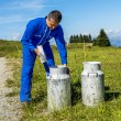 Stock Photo: Farmer with milk containers