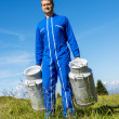 Foto Stock: Farmer with milk containers