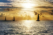 Sailboat and disherman at sunset — Stock Photo