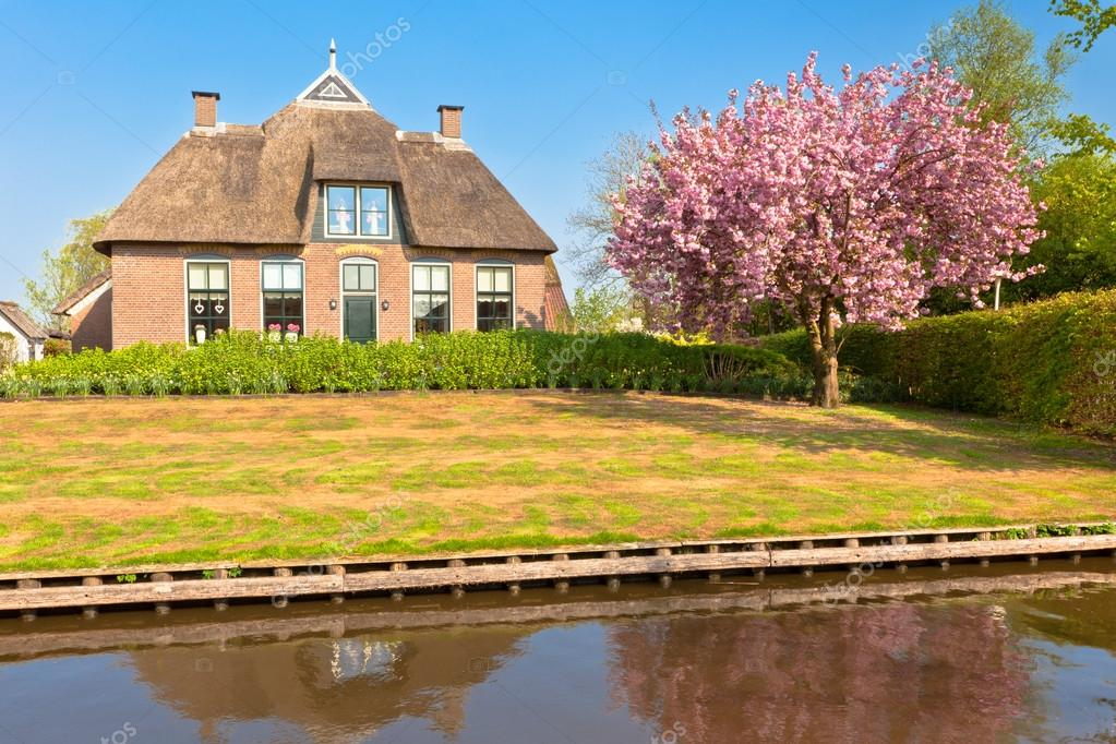 Beautiful traditional house with a thatched roof in a Dutch town of Giethoorn at spring — Stock Photo #12780816