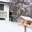 Birdhouse near snowy house — Stock Photo