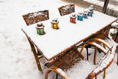 Color lamps on street cafe table at snow winter — Stock Photo