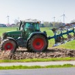 Tractor with plowes on the spring field. - Stock Photo