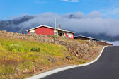 Roten häuschen und neuen asphaltstraße in ost-island — Stockfoto