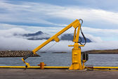 Fishing crane in small seaside Iceland town harbor. — Stock Photo