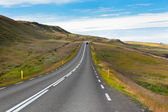 Highway through Icelandic landscape under a blue summer sky. — Stock Photo