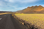 Highway through lava field landscape under a blue summer sky — Stock Photo