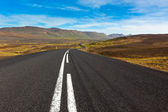 Highway through gravel lava field landscape under a blue summer — Stock Photo
