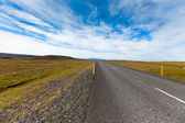 Highway through Icelandic landscape under a blue summer sky with — Stock Photo