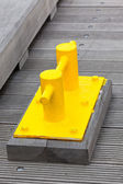 Closeup of Bright Yellow Boat Cleat on a dock pier — Stock Photo