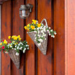 Stock Photo: Flowers in wicker pots on a icelandic wooden house