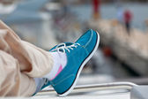 A pair of human legs in pants and bright blue topsiders — Stock Photo