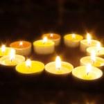Group of burning candles on black background. — Stock Photo