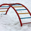 Empty swing-set covered with snow in winter - Stock Photo