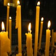 Stock Photo: Close up view of candles cutting through darkness.