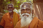 Holy Sadhu men in saffron color clothing blessing in Shiva Temple. — Stock Photo