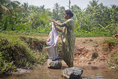 Indian woman washes her clothes — Stock Photo