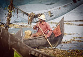 Fisherman fishing in wooden boat — Stock Photo