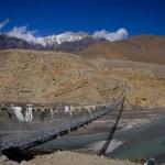 Bridge across mountain Nepal river — Stock Photo