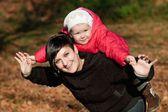 Giovane madre e la sua ragazza bambino divertirsi in autunno — Foto Stock