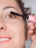 Young beautiful girl applying make-up — Stock Photo
