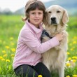 Girl hugging a big dog in an outdoor setting  — Lizenzfreies Foto