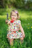 Niedliche kleine mädchen auf einer wiese voller blumen — Stockfoto