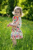 Portret van een klein meisje met een lolly — Stockfoto